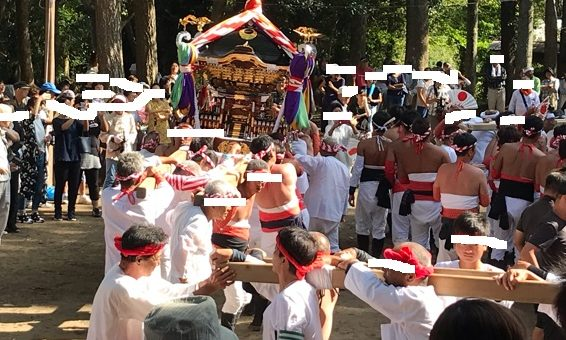 神輿を担いで神社の周りをまわっているところ