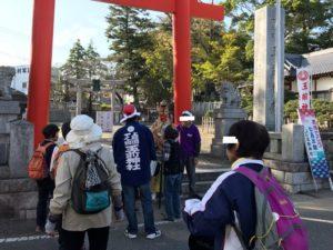 神社の鳥居の周りの人たちをお祓いする天狗